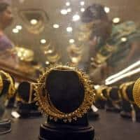 Gold inches down as dollar firms, but set for weekly gain